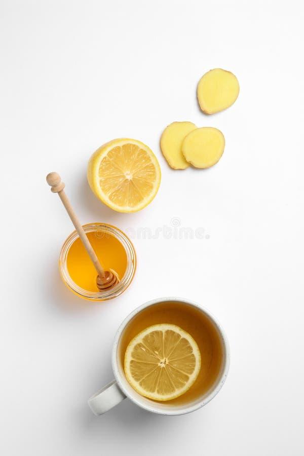 Samenstelling met citroenthee, honing en gember op witte achtergrond stock foto