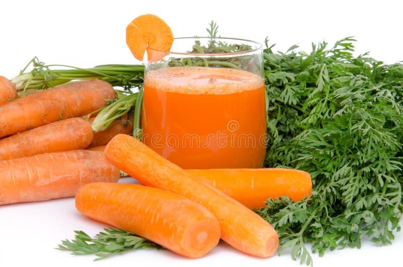 Samenstelling met een glas wortelsap en verse wortelen stock foto's