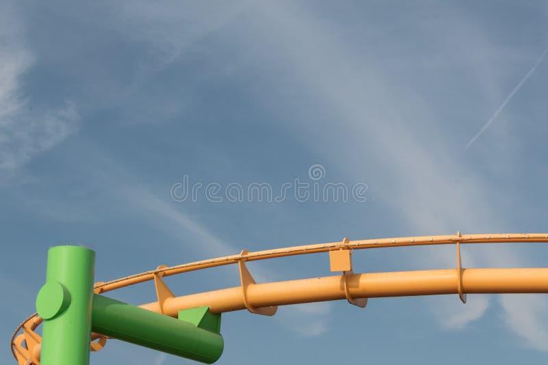 Samenstelling met groene en gele geschilderde Carnaval-rit tegen een blauwe hemel met wispy wolken, exemplaarruimte royalty-vrije stock afbeelding