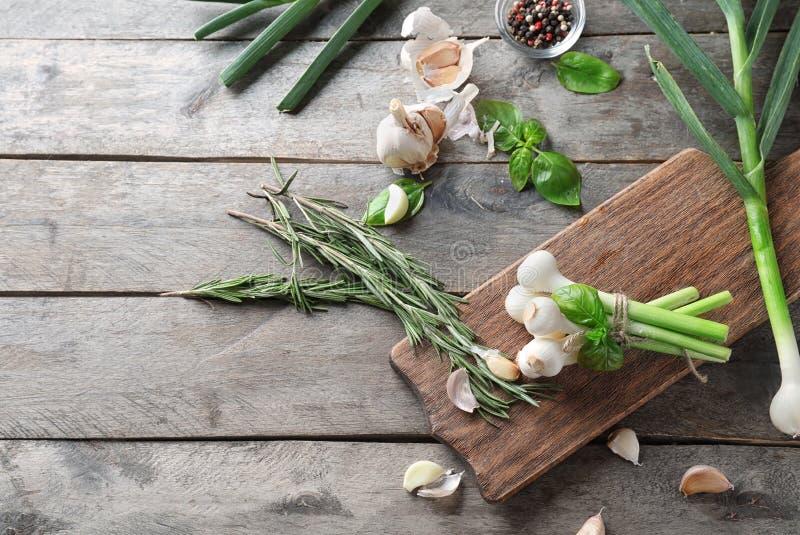 Samenstelling met groene ui en verse kruiden op houten achtergrond stock foto