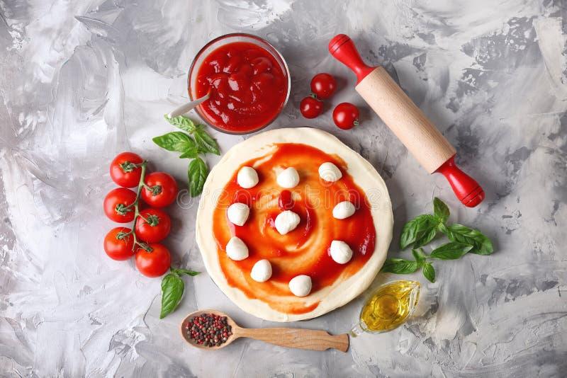 Samenstelling met groene verse basilicum en ingrediënten voor pizza op grijs royalty-vrije stock fotografie