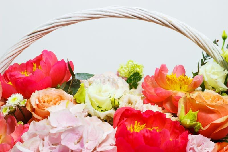 Samenstelling met heldere kleuren van pioenen, lisianthus, rozen in een witte mand royalty-vrije stock afbeeldingen