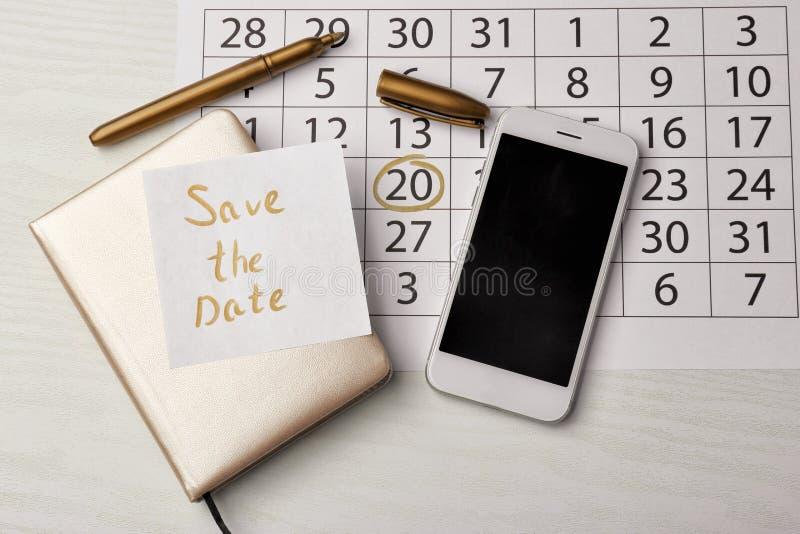 """Samenstelling met kalender, notitieboekje en blad van document met tekst \ """"sparen de datum \"""" op lijst stock foto"""