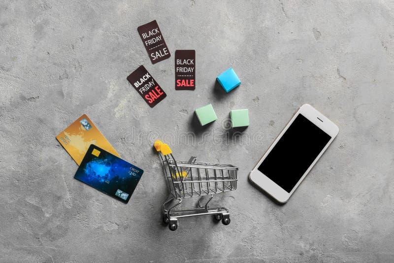 Samenstelling met kleine kar, mobiele telefoon en creditcards op grijze achtergrond Online Winkelend stock foto's