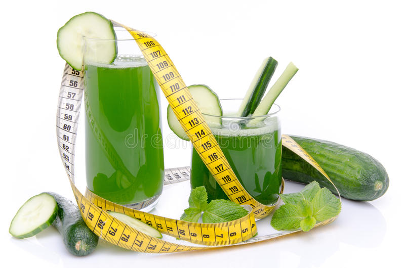 Samenstelling met komkommersap, verse komkommers en een band meas royalty-vrije stock foto's