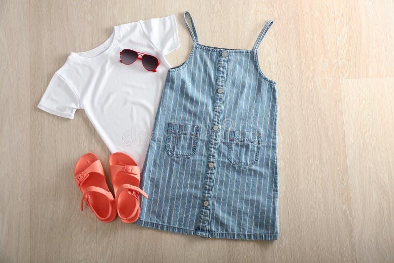 Samenstelling met leuke witte jong geitjet-shirt, sundress en schoenen op houten achtergrond stock fotografie