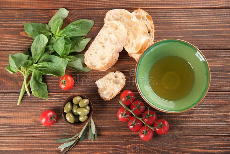 Samenstelling met olijfolie, vers brood, tomaten en kruiden op lijst, hoogste mening royalty-vrije stock foto's