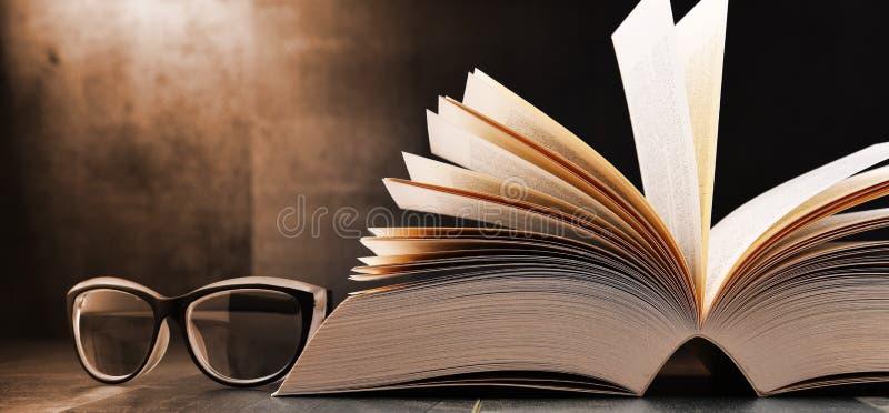 Samenstelling met open boek en glazen op de lijst stock foto