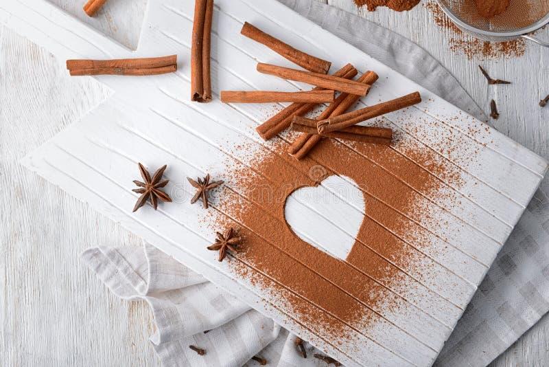 Samenstelling met pijpjes kaneel, anijsplantsterren en hart dat van poeder op houten raad worden gemaakt royalty-vrije stock afbeeldingen