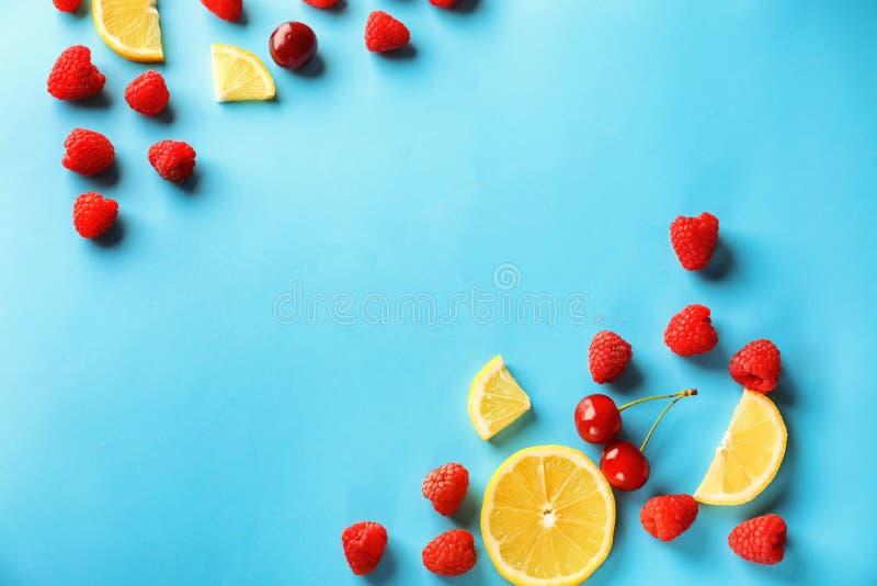 Samenstelling met rijpe aromatische frambozen, citroenplakken en kersen op kleurenachtergrond royalty-vrije stock afbeelding