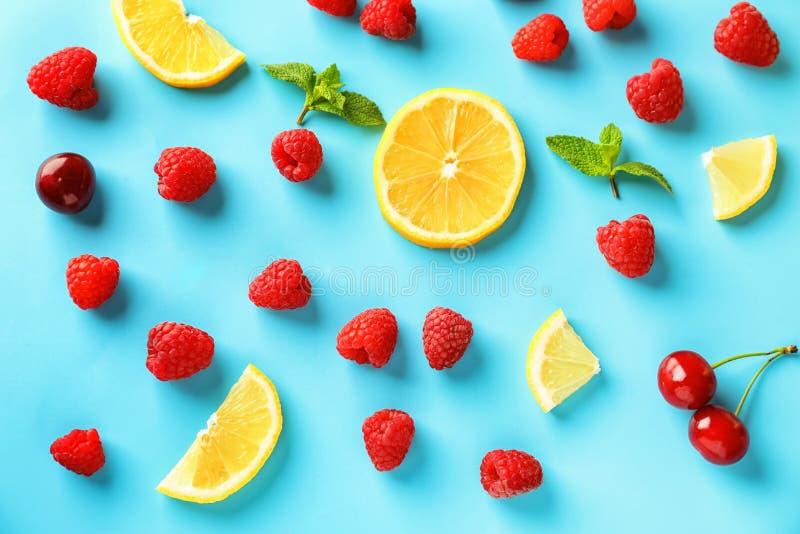 Samenstelling met rijpe aromatische frambozen, citroenplakken en kersen op kleurenachtergrond royalty-vrije stock afbeeldingen