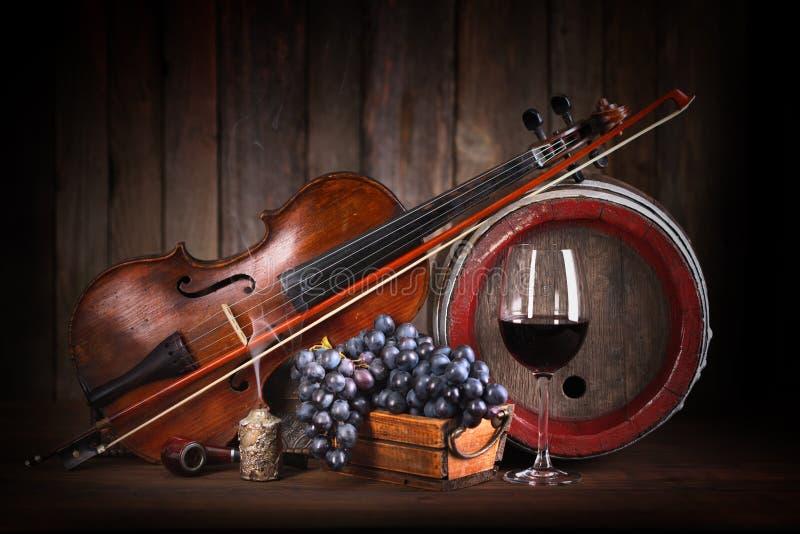 Samenstelling met rode druif, wijn, viool en vat stock foto's