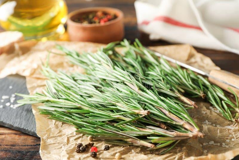 Samenstelling met rozemarijn, olie, peper, knoflook en mes op houten lijst stock afbeeldingen