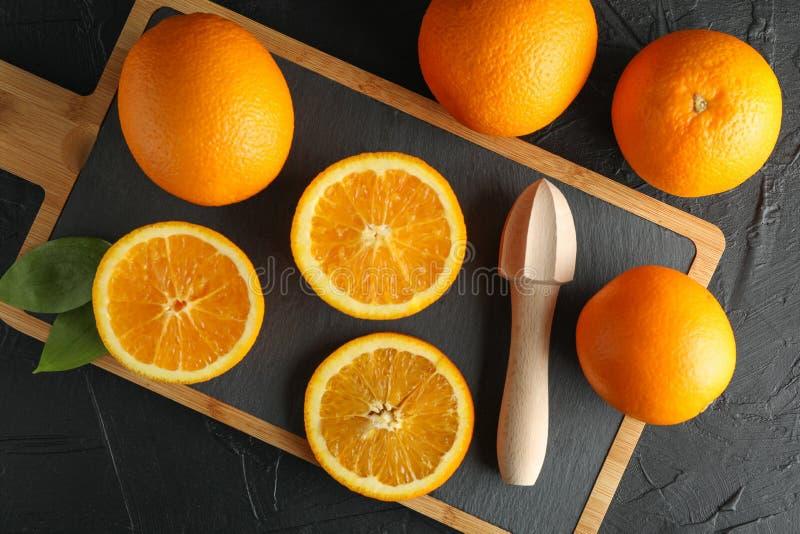 Samenstelling met scherpe raad, sinaasappelen en houten juicer stock fotografie
