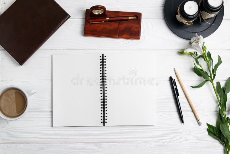 Samenstelling met van de het notitieboekjepen van het bureauonderwijs de stationaire bloemen van de het potloodkoffie stock foto