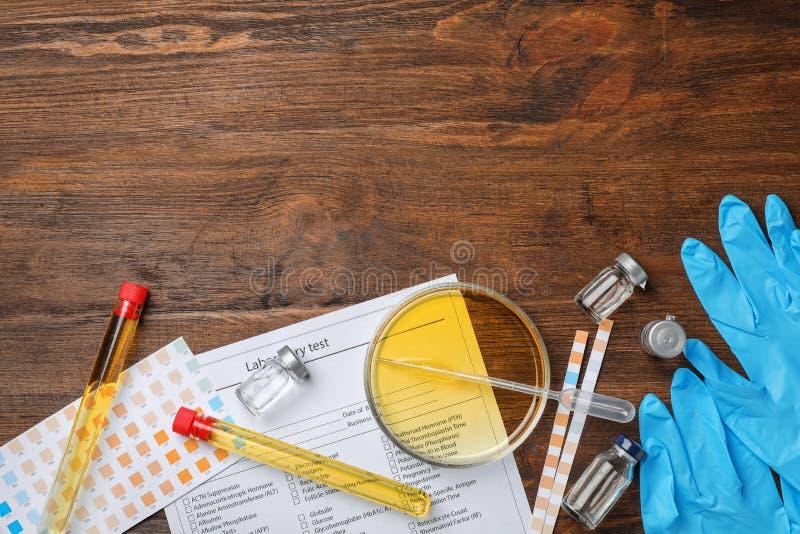 Samenstelling met van de laboratoriummateriaal en urine steekproeven op houten achtergrond Urologieconcept stock foto's