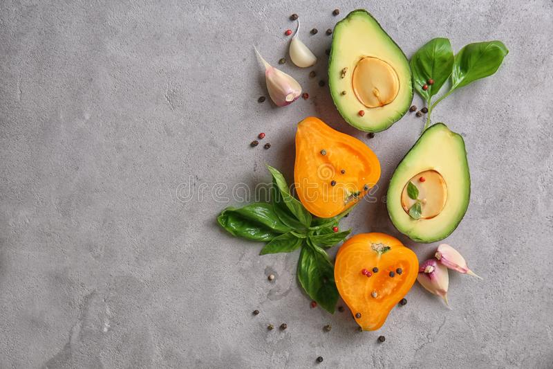 Samenstelling met verse rijpe avocado en tomaten op grijze geweven achtergrond stock fotografie