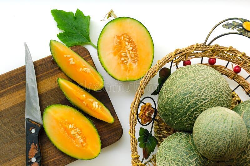 Samenstelling met verse rijpe meloenen op een witte achtergrond en een houten raad royalty-vrije stock afbeeldingen