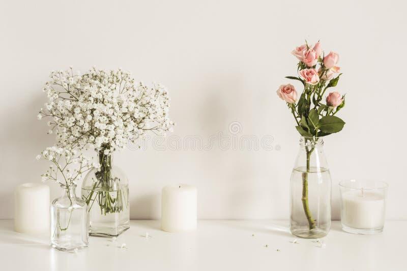 Samenstelling met witte en roze bloemen in glasflessen en kaarsen op de achtergrond van de lijstmuur Exemplaarruimte voor kunstwe royalty-vrije stock afbeeldingen