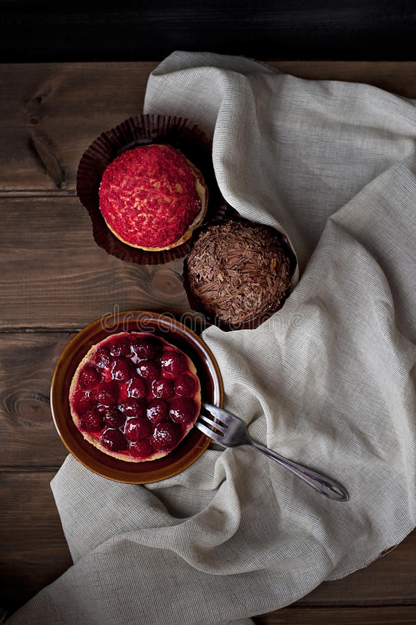 Samenstelling van aardbeicake, chocolademuffin en rode doughnut royalty-vrije stock foto's