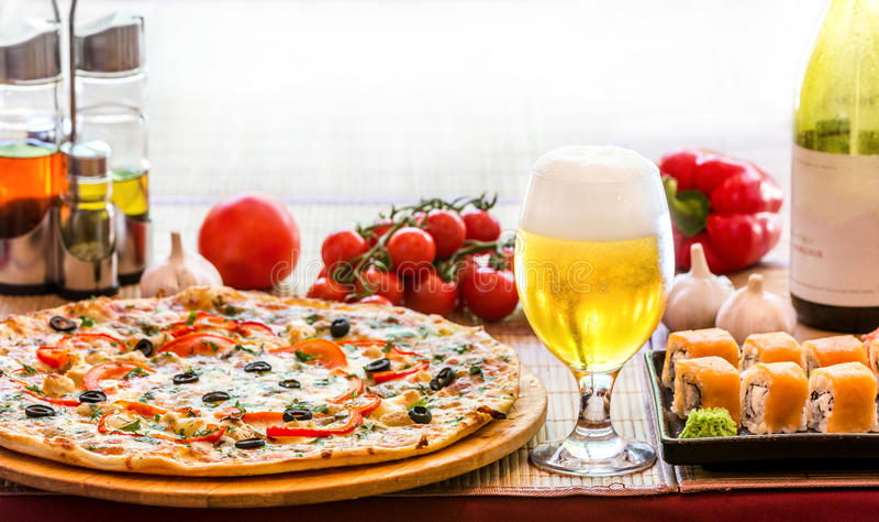 Samenstelling van biersushi en pizza stock foto