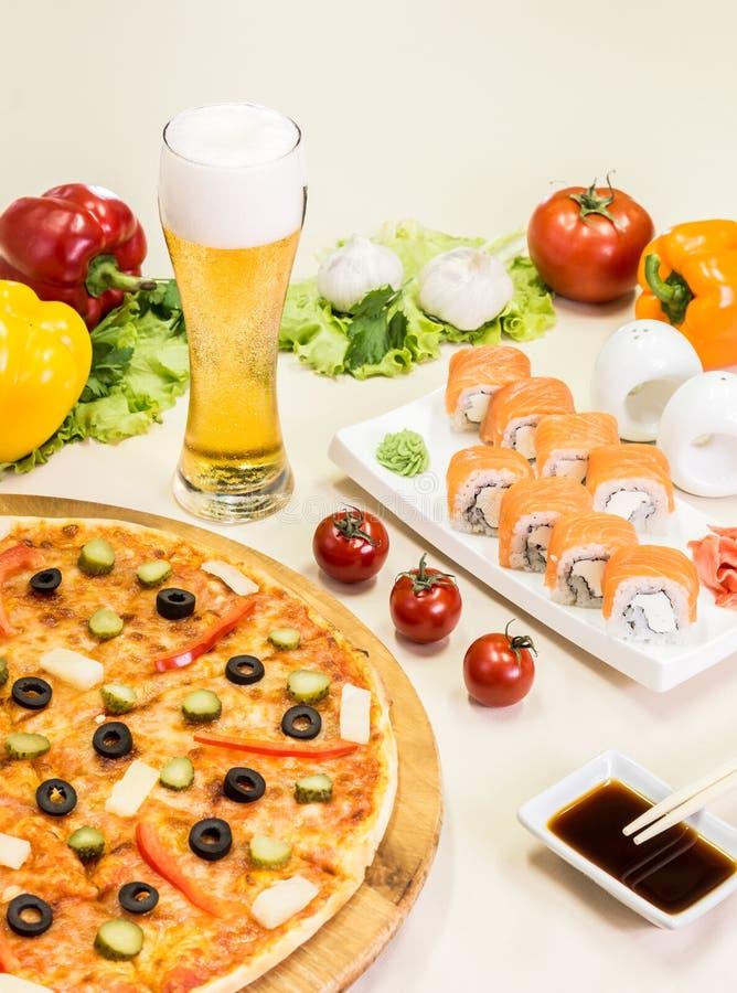 Samenstelling van biersushi en pizza stock afbeelding