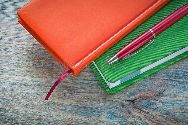 Samenstelling van de gesloten ballpoint van notaboeken op houten raad e royalty-vrije stock afbeelding