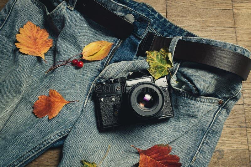 Samenstelling van de herfstbladeren, retro camera en jeans op houten achtergrond De hoogste vlakke mening, legt Gestemd warm Conc royalty-vrije stock foto