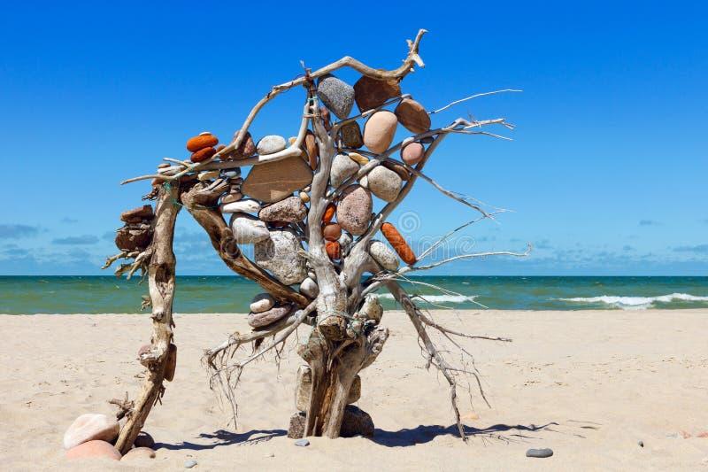 Samenstelling van de stenen en de droge boom op achtergrond van het overzees stock fotografie