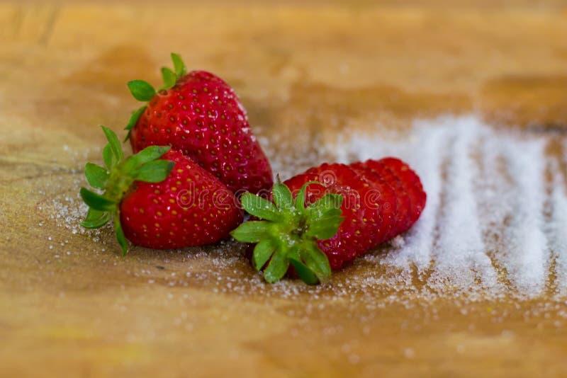 Samenstelling van drie aardbeien en suiker stock foto