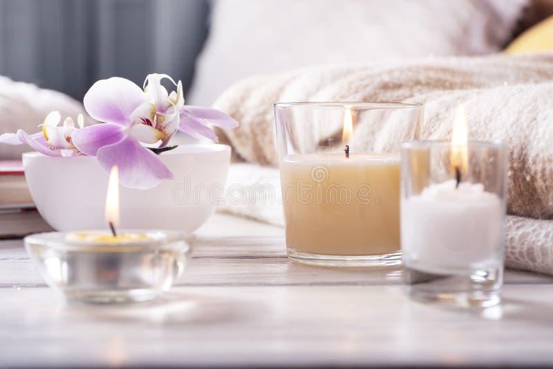 Samenstelling van drie kaarsen, orchidee in vaas op wit houten dienblad voor bed Omhoog sluiten huis binnenlandse detailes stock foto