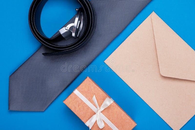 Samenstelling van grijze zilveren halsband, giftdoos, ambachtenvelop en riem op blauwe cyaanachtergrond Modieus man concept stock afbeelding
