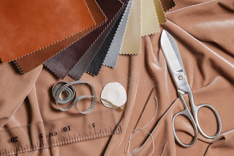 Samenstelling van het bewerken van hulpmiddelen en het naaien van toebehoren op een stoffenachtergrond Hoogste mening stock afbeeldingen