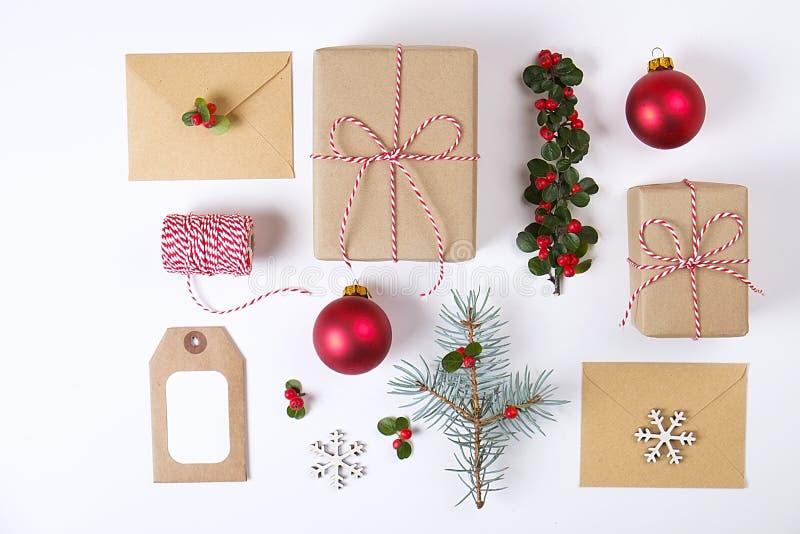 Samenstelling van het Kerstmis de gelukkige nieuwe jaar Kerstmisgiften, pijnboomtak, rode ballen, envelop, witte houten sneeuwvlo royalty-vrije stock afbeelding