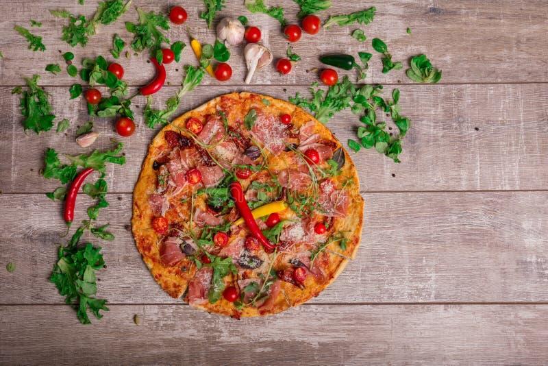 Samenstelling van Italiaans voedsel Groenten en pizza op een bruine achtergrond Italiaanse pizza met hete peper en kruidige saus stock foto