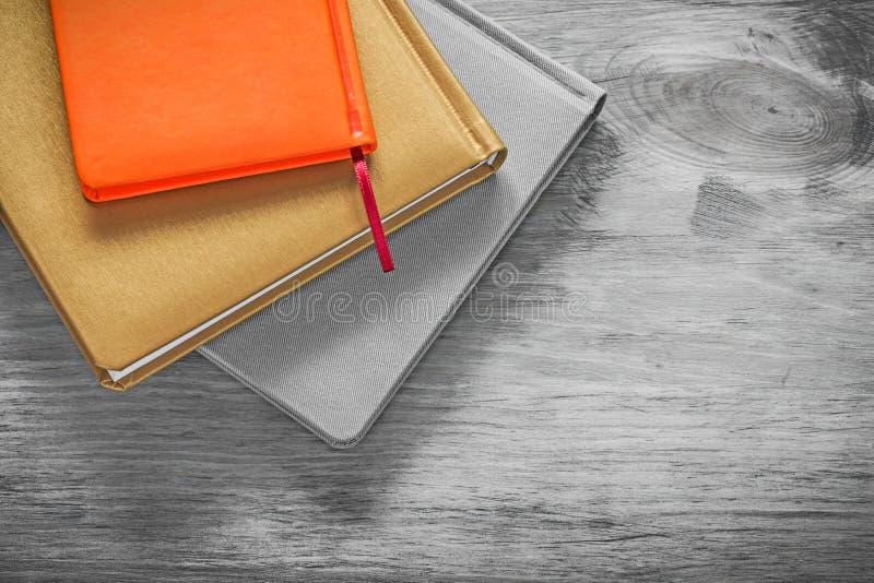Samenstelling van notitieboekjes op het houten concept van het raadsbureau stock fotografie