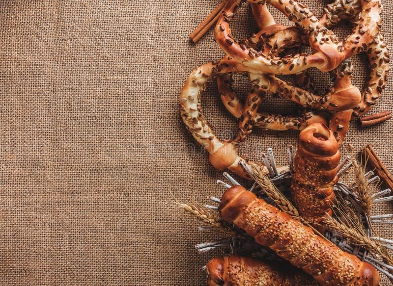 Samenstelling van pretzels met sesamzaden en worsten in deeg in mand op textiel De ruimte van het exemplaar royalty-vrije stock foto's