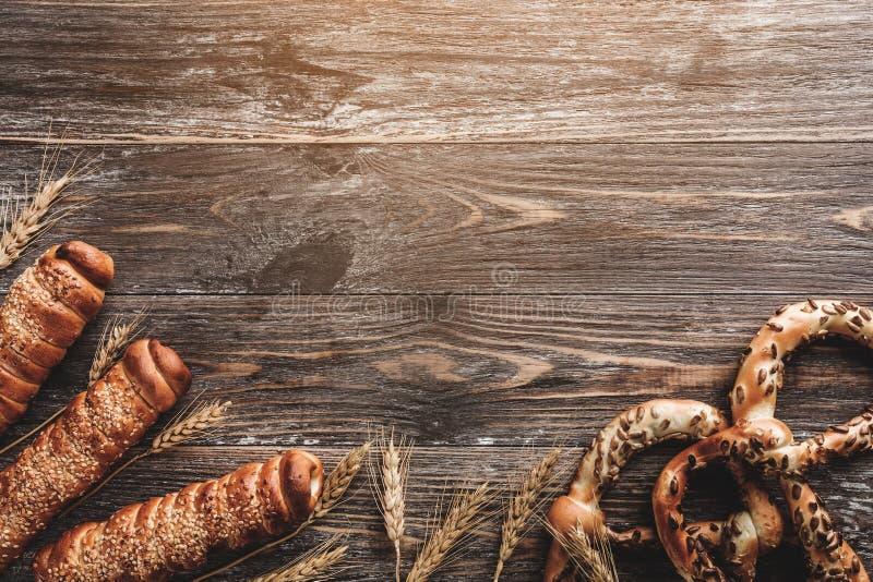 Samenstelling van pretzels met zonnebloemzaden, kruid van tarwe en worsten in deeg op houten lijst Exemplaar ruimte, lichteffect royalty-vrije stock foto