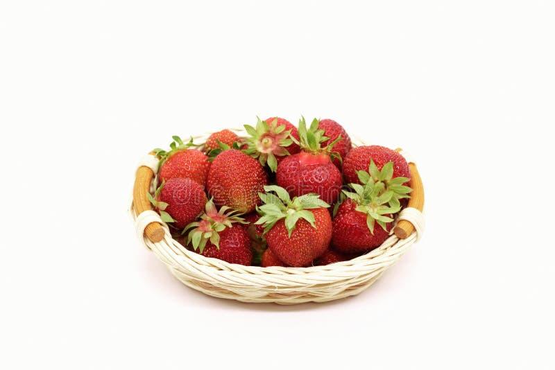 Samenstelling van rijpe aardbeien op een witte achtergrond in een rieten mand royalty-vrije stock afbeeldingen