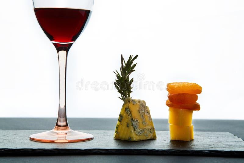 Samenstelling van traditionele aromatische kaas en droge abrikozen met glas rode wijn op witte achtergrond royalty-vrije stock fotografie