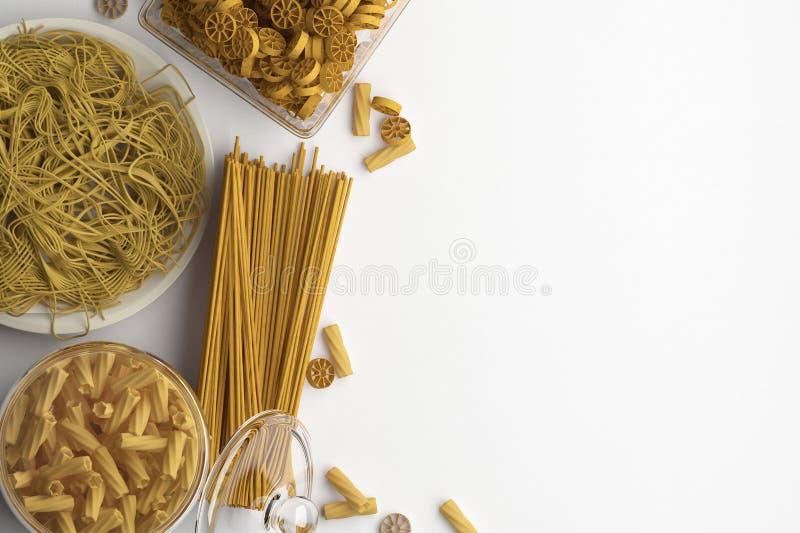 Samenstelling van verschillende types van droge en gekookte deegwaren en spaghetti op een witte achtergrond Banner met exemplaarr stock illustratie