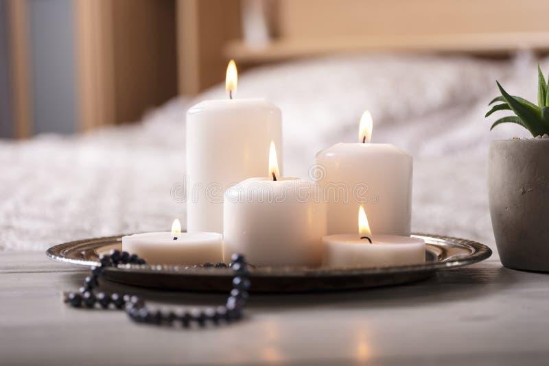 Samenstelling van witte brandende kaarsen op bedlijst in licht comfortabel slaapkamerbinnenland Selectieve nadruk royalty-vrije stock foto's