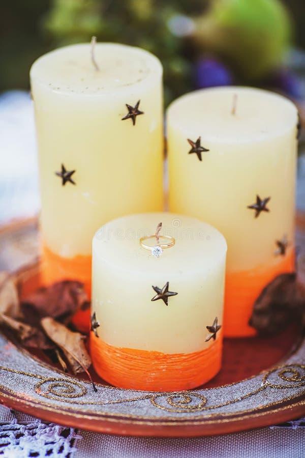 Samenstellings decoratieve kaarsen op dienblad met de uitstekende overeenkomst van de trouwringbruid met droge bladeren, gouden j stock afbeelding