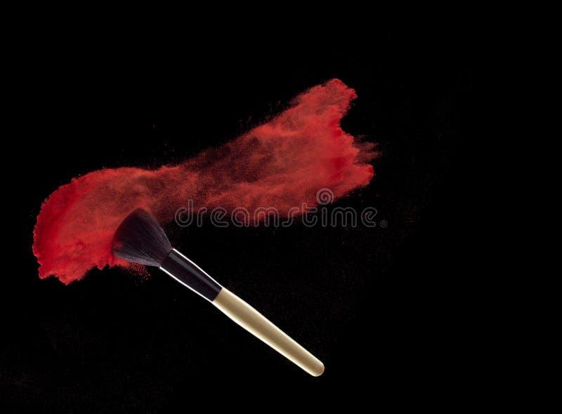 Samenstellingsborstel met rode poederexplosie op zwarte achtergrond stock afbeeldingen