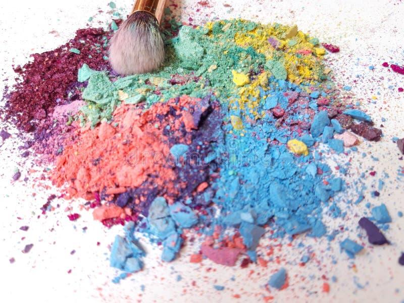 Samenstellingsborstel op gemengde kleurrijke verpletterde oogschaduw stock afbeeldingen