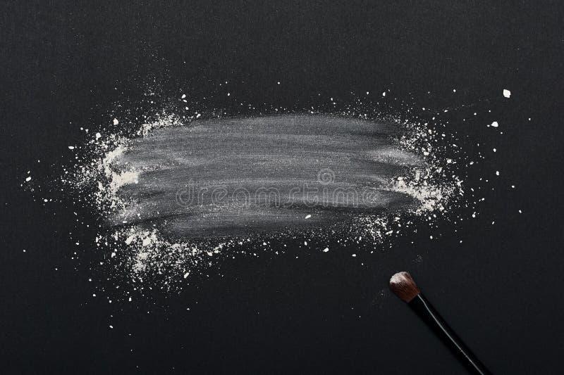 Samenstellingspoeder met schoonheidsborstel op zwarte Oppervlakte stock foto