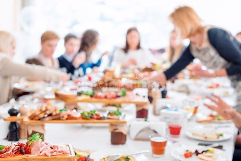 Samenvatting vage groep vrienden die in het restaurant samenkomen Onscherpe achtergrond van Kaukasische mensen die pret, het eten royalty-vrije stock afbeelding