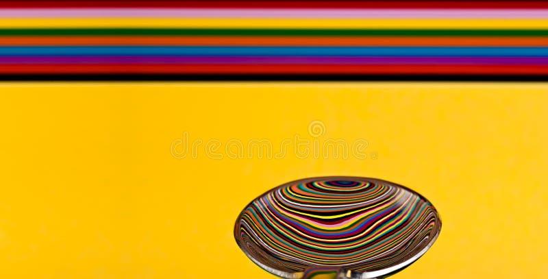 Samenvatting van een soeplepel die een weerspiegeling van een kleurrijke rug tonen royalty-vrije stock foto's