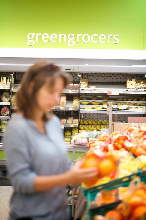 Samenvatting van mum die in een supermarktgroentehandelaar winkelen stock fotografie