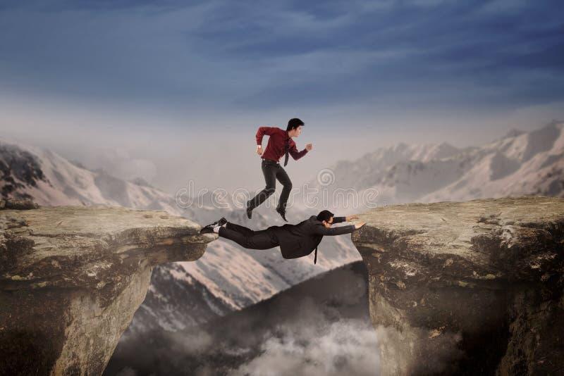 Samenwerking van twee zakenlieden door een hiaat stock foto